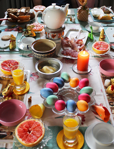 A table set for breakfast. Showing eggs, fruit, juice, cold meats, butter.