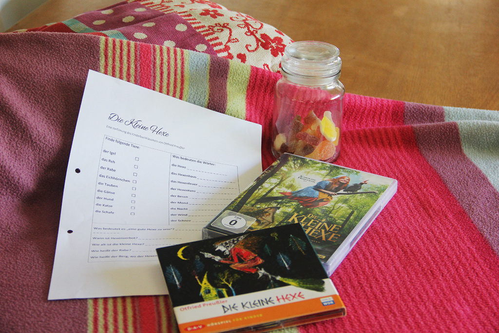 CD, DVD, piece of paper and a lolly jar on top of a colourful blanket